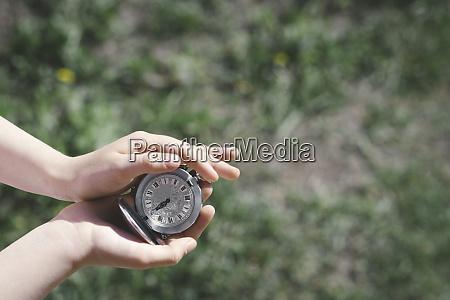 girls hands holding silver pocket clock