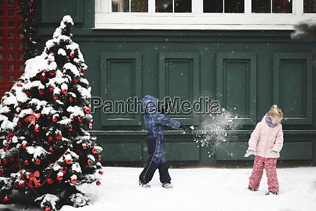 siblings having a snowball fight at