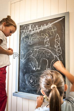 two girls drawing on blackboard