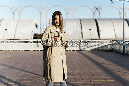 young blond woman using smartphone
