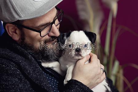 man stroking his pug