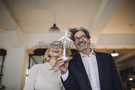 happy businessman and businesswoman holding wind