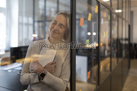 mature businesswoman with closed eyes leaning