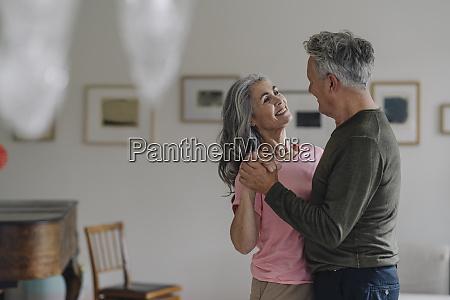 happy senior couple dancing in living