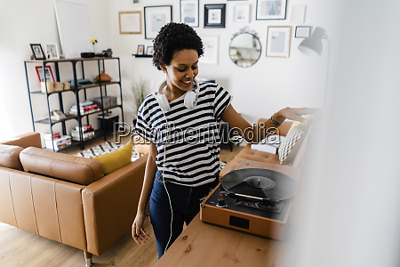young woman using record player at