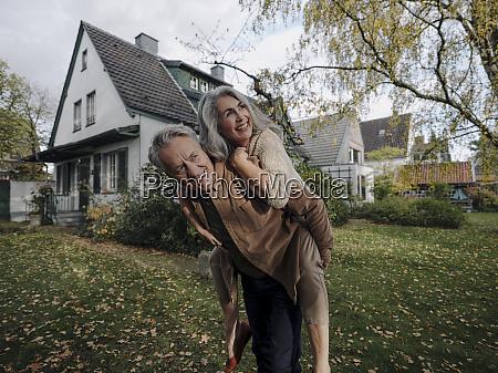 happy senior man carrying wife piggyback