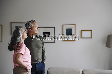 senior couple standing in living room