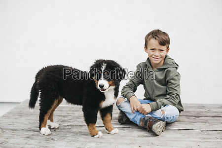 boy playing with his bernese mountain