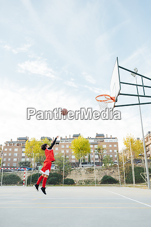 boy playing basketball on outdoor court
