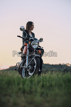 young woman with vintage motorbike in