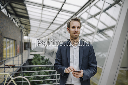 smiling businessman using cell phone in
