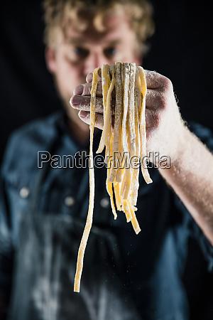 hobby chef holding fresh tagliatelle pasta