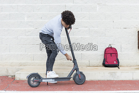 young man folding e scooter