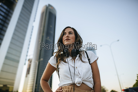 young woman with headphones around neck