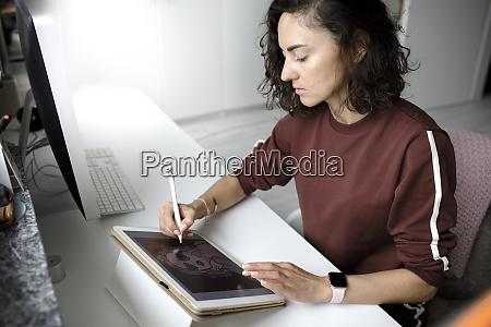 female web designer using tablet at