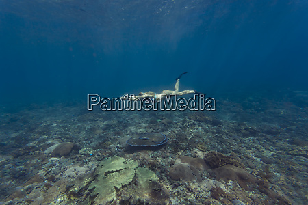 young woman diving nusa penida island