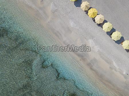 drone shot of yellow parasols arranged