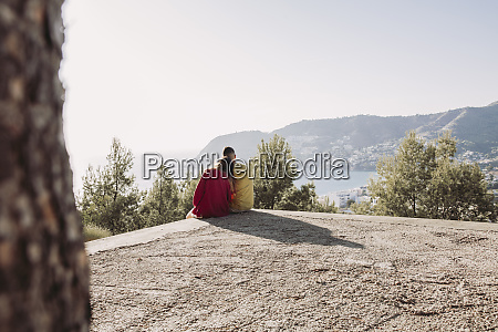 young couple sitting on viewpoint