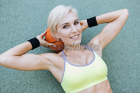 blonde woman lying on basketball