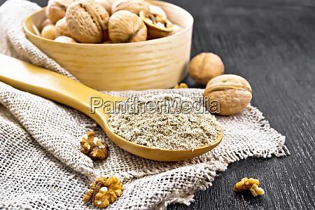 flour walnut in spoon on burlap