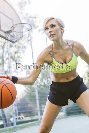 blonde woman playing basketball dribbling