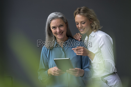 two smiling businesswomen sharing a tablet