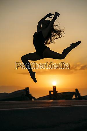 silhouette of ballerina daning at sunset