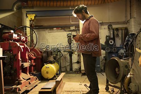 metal worker working in workshop using