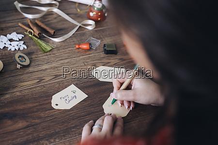 young woman writing christmas gift tags
