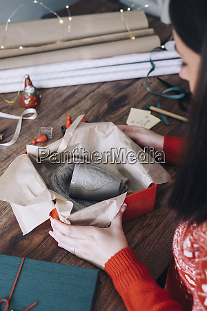 young woman packing christmas present