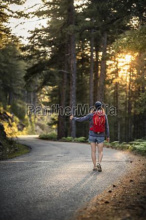 female hitchhiker on a road col