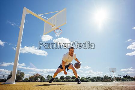 man playing basketball on yellow court