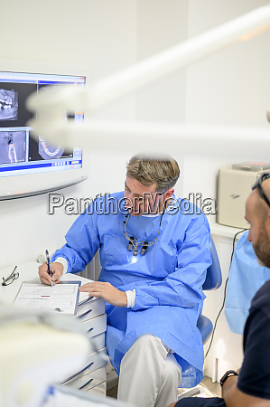 dentist surgeon chatting with patient writing