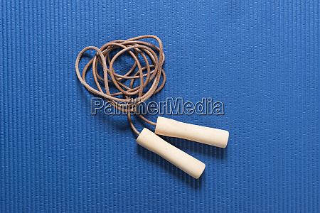 skipping rope on blue workout mat