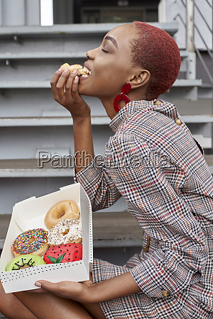 young woman eating a doughnut from