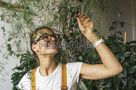 happy young woman caring for plants