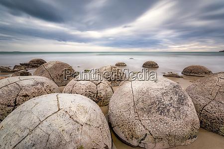 moeraki boulders on shore against cloudy