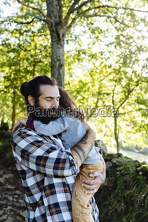 father holding kid in the forest