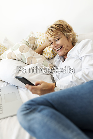 happy mature woman sitting on bed