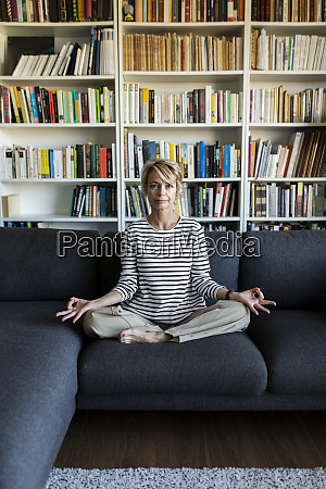 mature woman practicing yoga on couch