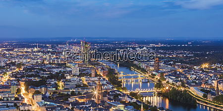 illuminated cityscape against blue sky at