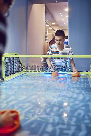 teenage boy playing air hockey in