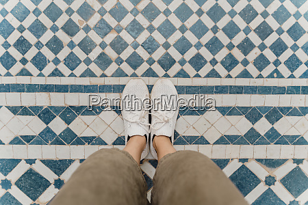 womans feet standing on traditionally tiled