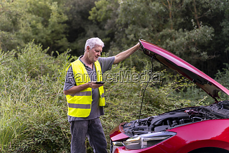 senior man standing at his broken