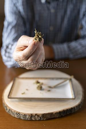 senior man at home rolling marihuana