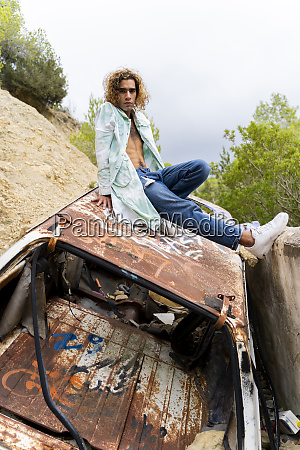 young blond man sitting on junk