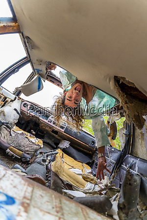 young blond man in junk car