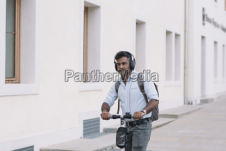 casual businessman wearing headphones riding e