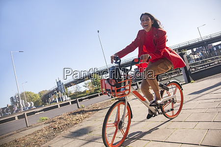 young woman riding through the city