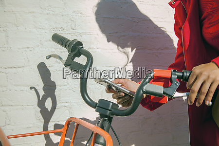 young woman using rental bike with